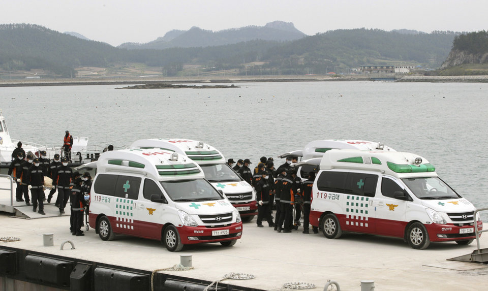 Photo - Emergency workers carry the bodies of passengers aboard the Sewol ferry which sank in the water off the southern coast, upon their arrival at a port in Jindo, South Korea, Tuesday, April 22, 2014. As divers continue to search the interior of the sunken ferry, the number of confirmed deaths has risen, with over 200 other people still missing. (AP Photo/Ahn Young-joon)