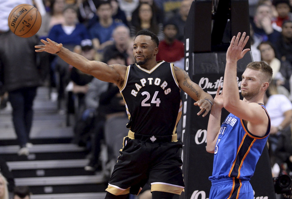 Photo - Toronto Raptors guard Norman Powell (24) moves the ball away from Oklahoma City Thunder forward Domantas Sabonis (3) during the second half of an NBA basketball game Thursday, March 16, 2017, in Toronto. (Nathan Denette/The Canadian Press via AP)