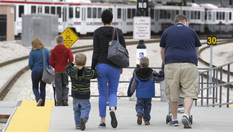 Photo - Commuters walk down the track after getting off the
