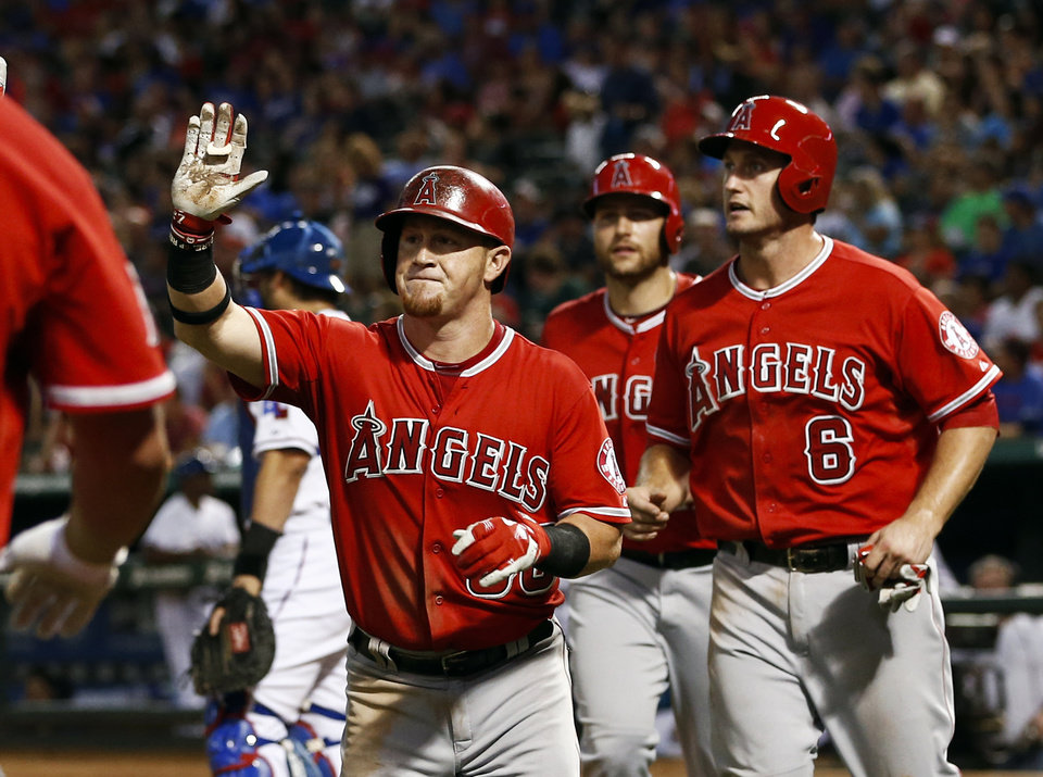 Photo - Los Angeles Angels' Kole Calhoun, left, is congratulated as he heads to the dugout after hitting a three-run home run scoring David Freese (6) and Chris Iannetta against the Texas Rangers during the fifth inning of a baseball game, Friday, Aug. 15, 2014, in Arlington, Texas. (AP Photo/Jim Cowsert)
