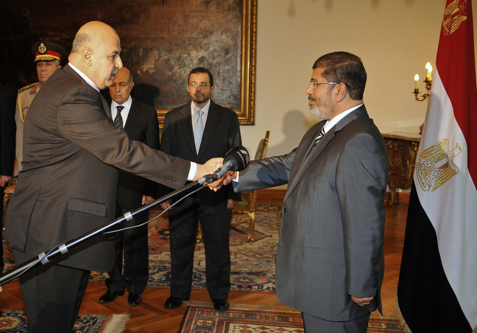 Photo - FILE - In this Sunday, Aug. 12, 2012 file photo released by the Egyptian Presidency, Egyptian President Mohammed Morsi swears in newly-appointed vice president, a former senior judge, Mahmoud Mekki, in Cairo, Egypt. Egypt's state TV says Vice President Mahmoud Mekki has resigned. Mekki's Saturday, Dec. 22, 2012 resignation was announced with more than five hours to go of voting in the second and final phase of a referendum on a disputed, Islamist-backed constitution.  (AP Photo/Egyptian Presidency, File)