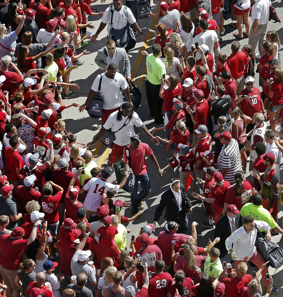 Photo - Fans line up to greet the Oklahoma football team, including Blake Bell, bottom right, and Trevor Knight during the team's Walk of Champions before a college football game between the University of Oklahoma Sooners (OU) and the Louisiana Tech Bulldogs at Gaylord Family-Oklahoma Memorial Stadium in Norman, Okla., on Saturday, Aug. 30, 2014. Photo by Bryan Terry, The Oklahoman