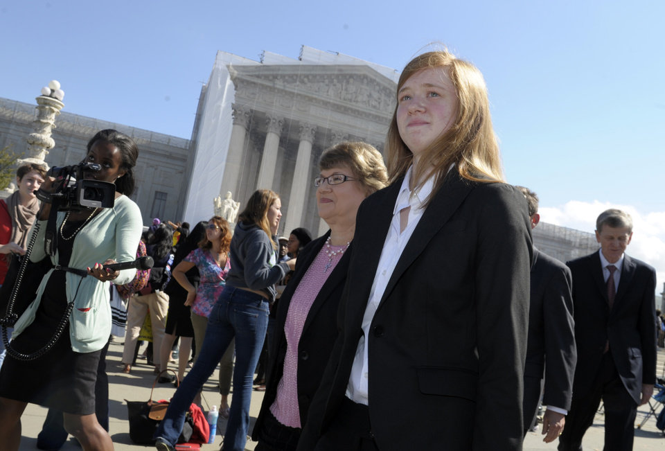 Photo -   Abigail Fisher, right, who sued the University of Texas, walks outside the Supreme Court in Washington, Wednesday, Oct. 10, 2012. The Supreme Court is taking up a challenge to a University of Texas program that considers race in some college admissions. The case could produce new limits on affirmative action at universities, or roll it back entirely. (AP Photo/Susan Walsh)