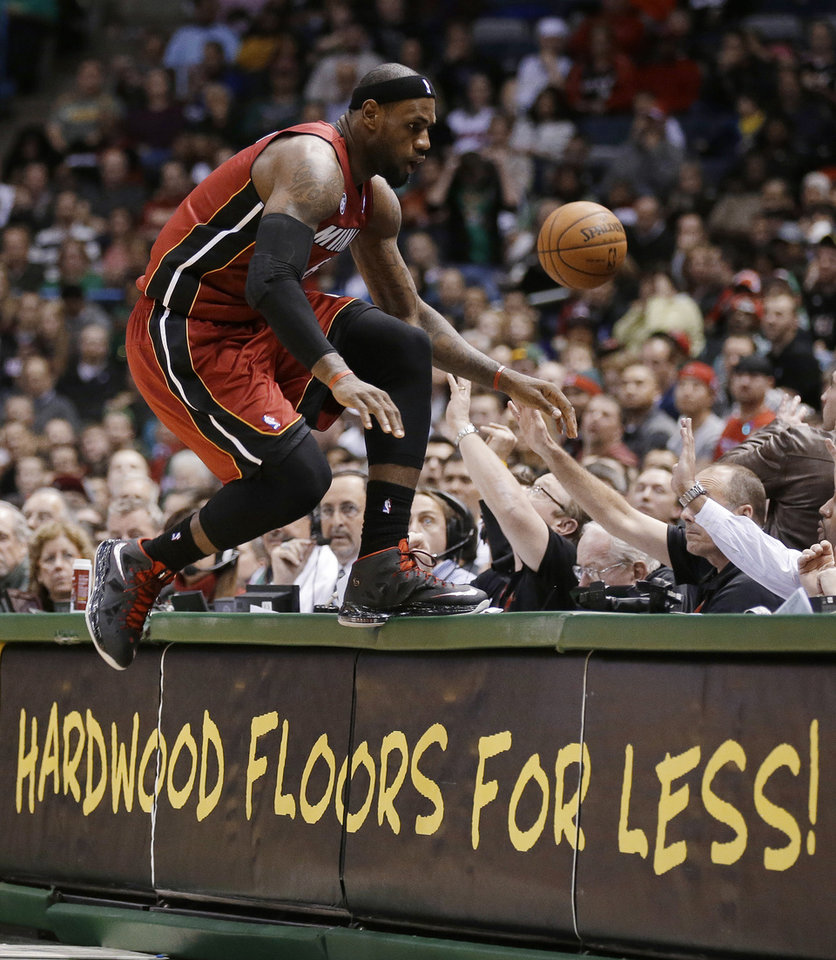 Photo - Miami Heat's LeBron James jumps onto a table while trying to save a ball going out of bounds against the Milwaukee Bucks in the second half of an NBA basketball game Friday, March, 15, 2013, in Milwaukee. (AP Photo/Jeffrey Phelps)