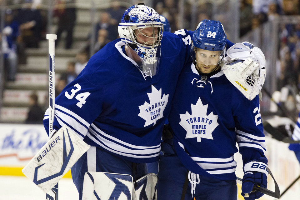 Toronto Maple Leafs goaltender James Reimer (34) is helped off the ice by John-Michael Liles during the second period of their NHL hockey game against the Philadelphia Flyers, Monday, Feb. 11, 2013, in Toronto. (AP Photo/The Canadian Press, Chris Young)
