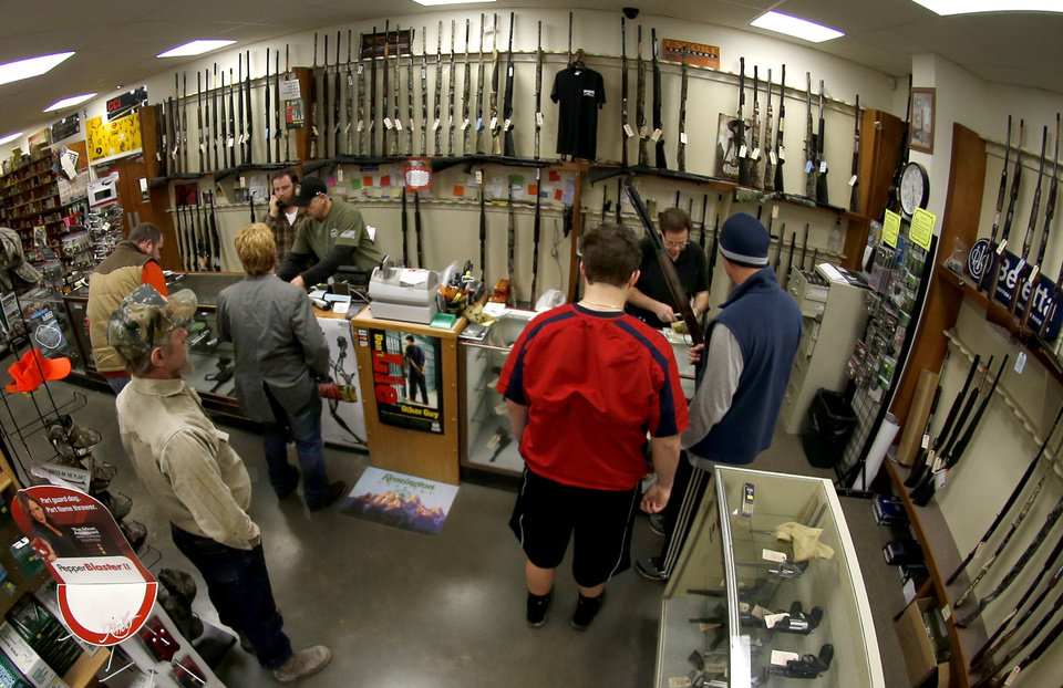 FILE - In this Jan. 16, 2013 file photo, taken with a fisheye lens, customers line up at the gun counter at Duke\'s Sport Shop in New Castle, Pa. The FBI posted new data for gun background checks covering through January 2013 that says gun checks *dropped* more than 10 percent nationwide, from roughly 2.8 million in December 2012 to 2.5 million in January 2013. (AP Photo/Keith Srakocic, File)