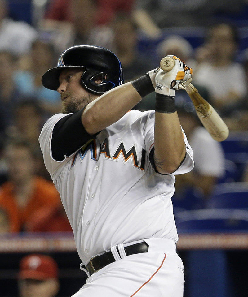 Photo - Miami Marlins' Casey McGehee follows through on a base hit against the Philadelphia Phillies in the first inning of a baseball game in Miami, Tuesday, May 20, 2014. Derek Dietrich scored on the single. (AP Photo/Alan Diaz)