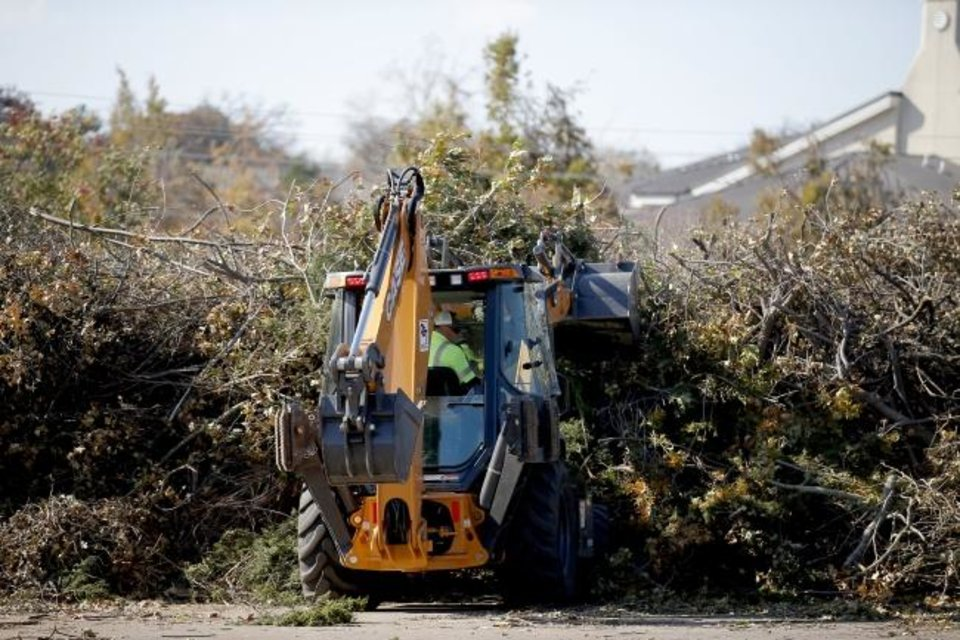 Photo -  Landfills are taking debris free of charge from 8 a.m. to 4 p.m. every Saturday through Jan. 2.  Here, a worker uses a backhoe to move tree debris from the recent ice storm at a drop-off location at Hafer Park in Edmond.  [Sarah Phipps/The Oklahoman]