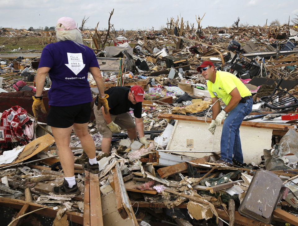 Michael Reed and Brett Droy from the First Baptist Church of Moore team with Toodie May, a volunteer with a Michigan group, Disaster Relief at Work (DRAW) to sift through the debris of this destroyed home. Volunteers from various parts of the country joined Oklahomans in assisting residents on Saturday, May 25, 2013, doing whatever was needed to remove debris and salvage items from this neighborhood east of Santa Fe, north of SW 19 Street. An EF5 tornado leveled many neighborhoods in Moore and southwest Oklahoma City last Monday. Photo by Jim Beckel, The Oklahoman.