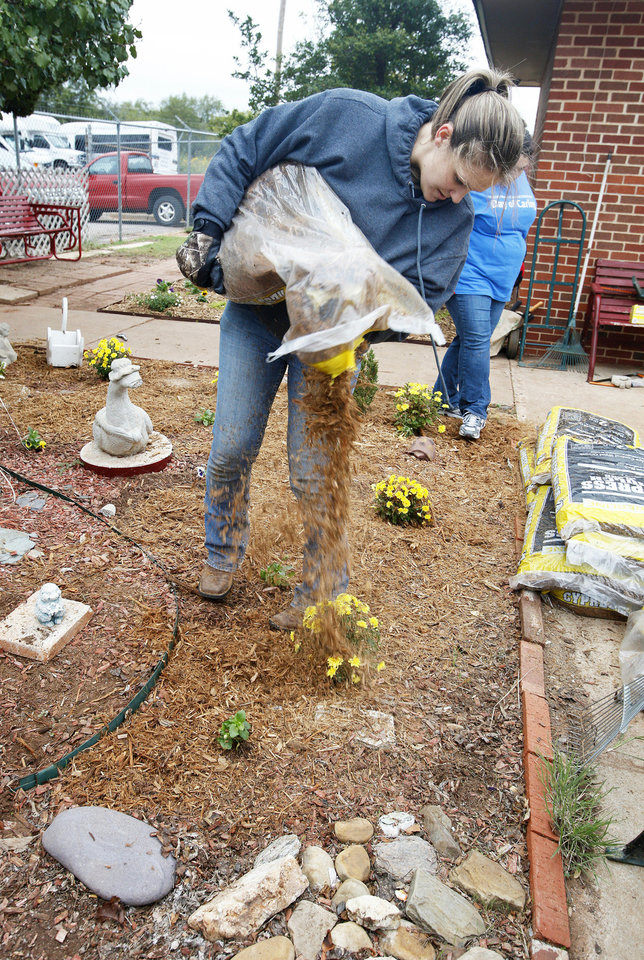 Above: Volunteer Amber Starkey, of Crescent, spreads mulch while doing landscape work at the Oklahoma Foundation for the Disabled during the annual Day of Caring for United Way in Oklahoma City.