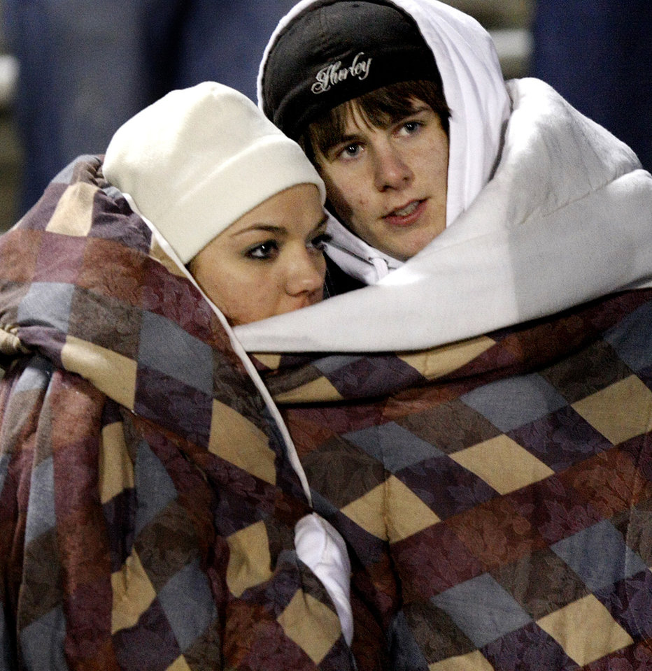 Photo - Kingfisher football fans tries to stay warm during the Class 2A State semifinal football game between Millwood High School and Kingfisher High School on Saturday, Dec. 5, 2009, in Yukon, Okla. 