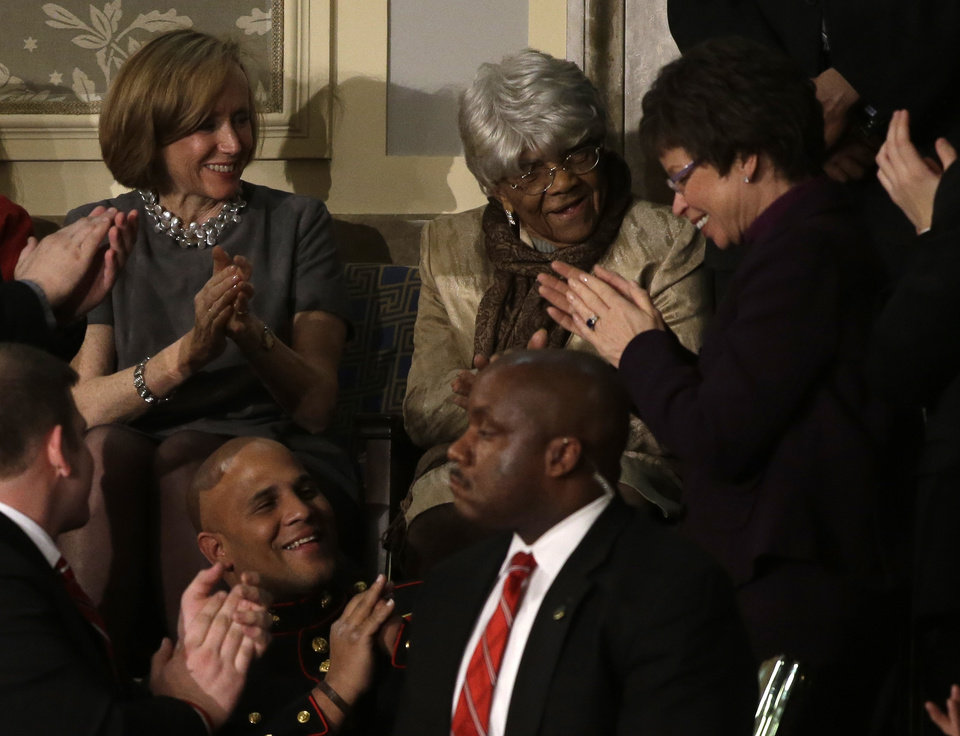 Photo - Desiline Victor, 102, of Miami is applauded by White House senior adviser Valerie Jarrett, right, and others, during President Barack Obama's State of the Union address during a joint session of Congress on Capitol Hill in Washington, Tuesday Feb. 12, 2013. (AP Photo/Jacquelyn Martin)