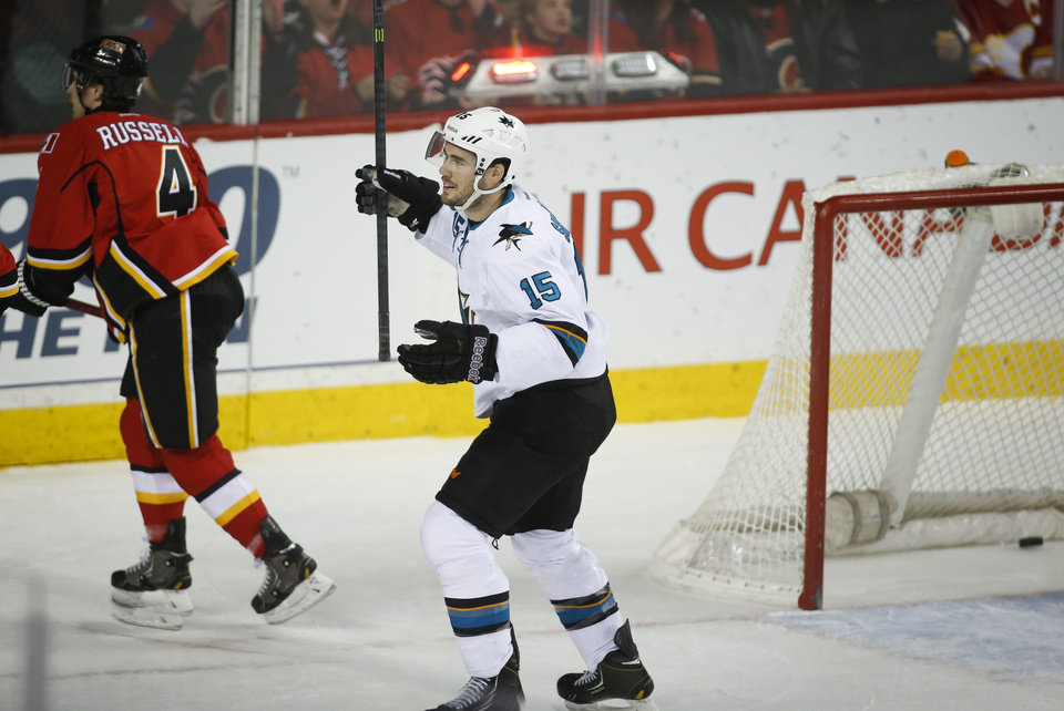Photo - San Jose Sharks' James Sheppard, right, celebrates his goal as Calgary Flames' players skate away during first period NHL hockey action in Calgary, Monday, March 24, 2014.  (AP Photo/The Canadian Press, Jeff McIntosh)