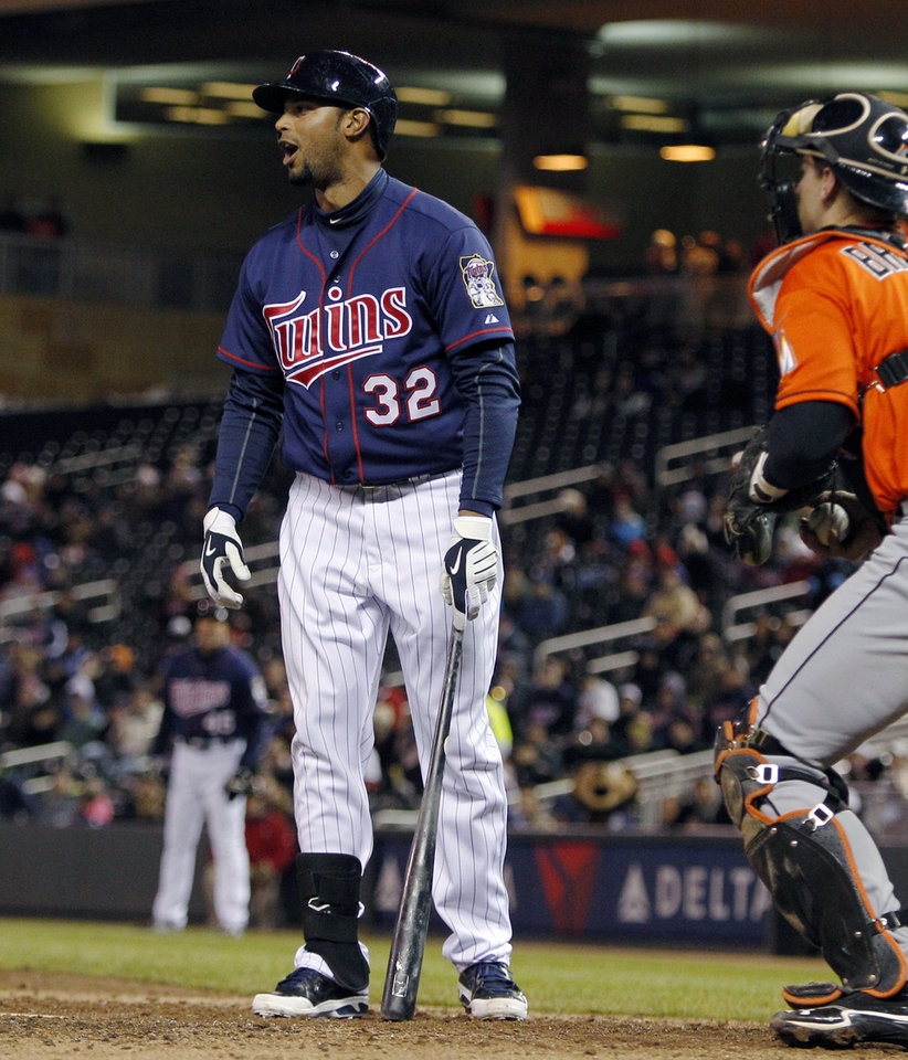 Photo - Minnesota Twins' Aaron Hicks (32) reacts after striking out looking against Miami Marlins starting pitcher Ricky Nolasco as Marlins catcher Rob Brantly watches during the fourth inning in the second baseball game of a doubleheader Tuesday, April 23, 2013, in Minneapolis. (AP Photo/Genevieve Ross)