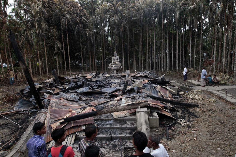People look at a Buddhist temple which was torched in an overnight weekend attack in Ramu in the coastal district of Cox's Bazar, Bangladesh, Tuesday, Oct. 2, 2012. About 1,000 Buddhist families fled their villages after rioters burned at least 10 Buddhist temples and 40 homes and looted shops in anger over a Facebook photo of a burned Quran. Authorities in Bangladesh have ordered security officials to remain alert around official camps of Rohingya Muslims following the attacks.(AP Photo/A.M.Ahad)