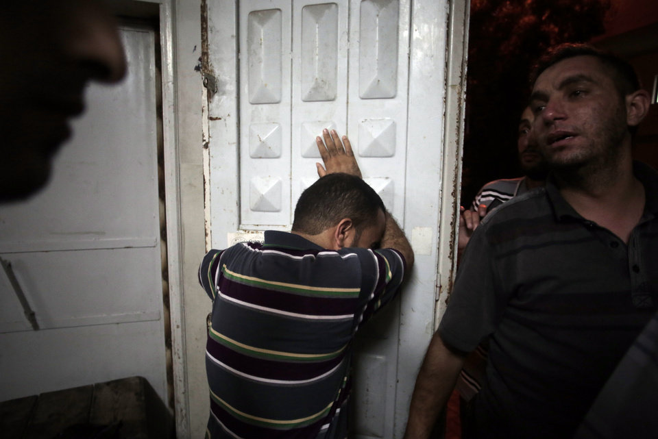 Photo - Palestinians mourn their relatives in the morgue of the Shifa hospital in Gaza City on Saturday, July 12, 2014. Over a dozen Palestinians were killed in an Israeli strike on a house, hospital officials said. Ignoring international appeals for a cease-fire, Israel on Saturday widened its range of Gaza bombing targets to civilian institutions with suspected Hamas ties and announced it would hit northern Gaza