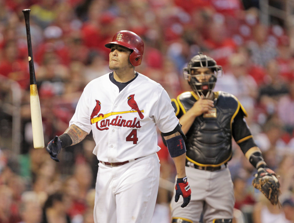 Photo - St. Louis Cardinals' Yadier Molina (4) tosses his bat in frustration after being called out on strikes as Pittsburgh Pirates catcher Russell Martin looks on in the fourth inning of a baseball game, Tuesday, July 8, 2014 in St. Louis. (AP Photo/Tom Gannam)