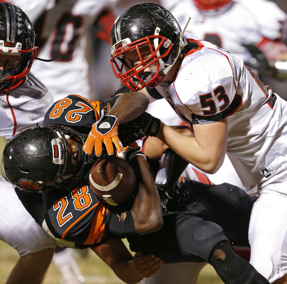 Photo - Douglass' Anthony Jackson is brought down by Locust Grove's Alex Hix during their high school football playoff game at Douglass in Oklahoma City, Friday, Nov. 28, 2014. Photo by Bryan Terry, The Oklahoman
