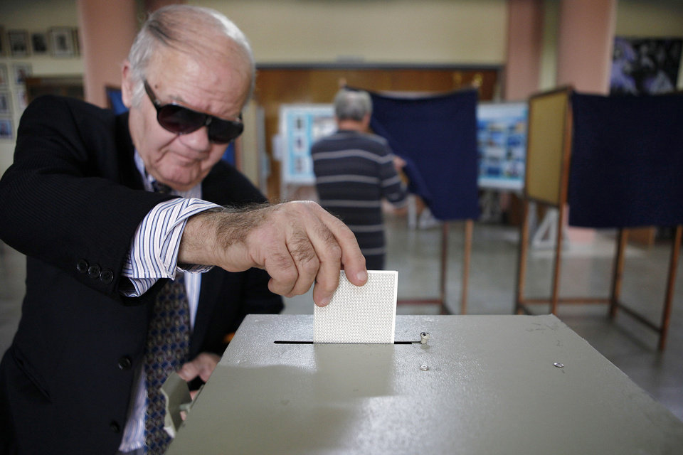 Photo - A man votes in the presidential election in southern port city of Limassol, Cyprus, Sunday, Feb. 24, 2013. Opposition party leader Nicos Anastasiades garnered 45.46 per cent of the vote in the first round of voting, some 18 points over communist-backed Stavros Malas. (AP Photo/Petros Karadjias)