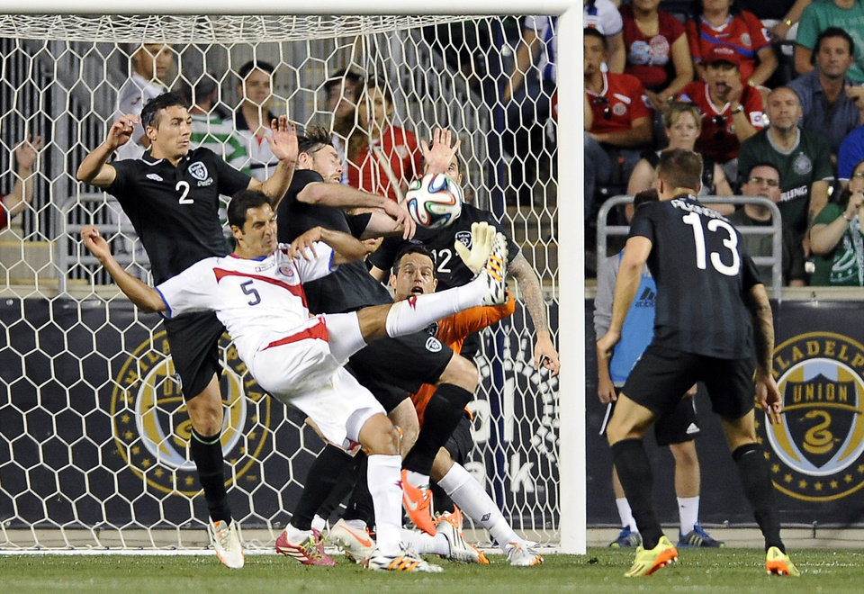 Photo - Costa Rica's Celso Borges (5) takes a shot on goal as Ireland's Stephen Kelly (2), Richard Keogh, middle and goal keeper David Forde defend during the first half of an international friendly soccer match on Friday, June 6, 2014, in Chester, Pa. (AP Photo/Michael Perez)