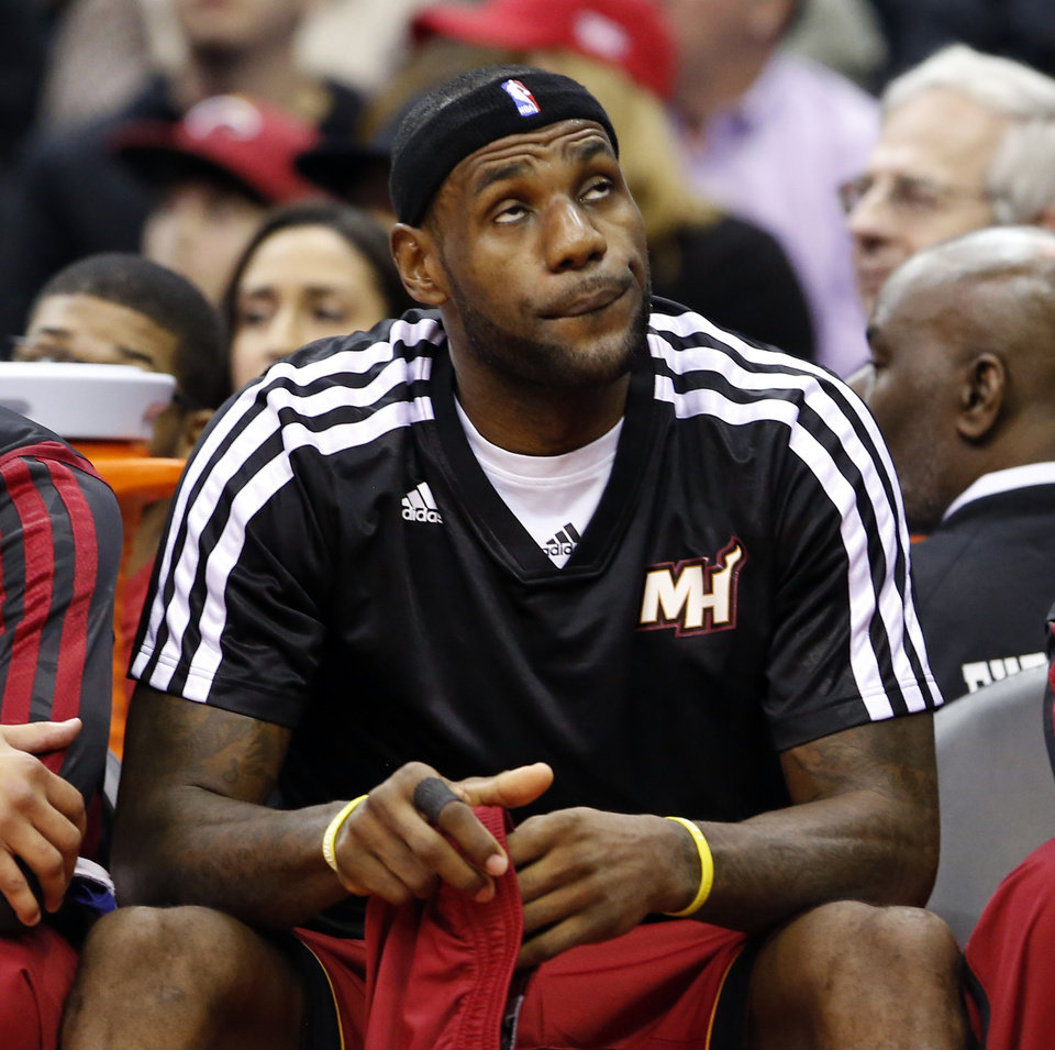 Photo - Miami Heat forward LeBron James (6) sits on the bench in the first half of an NBA basketball game against the Washington Wizards, Wednesday, Jan. 15, 2014, in Washington. The Wizards won 114-97. (AP Photo/Alex Brandon)