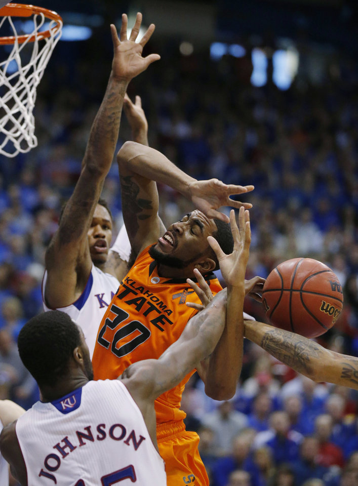 Oklahoma State forward Michael Cobbins (20) scrambles for the ball in the lane with Kansas guards Elijah Johnson, foreground, Ben McLemore during the second half of an NCAA college basketball game in Lawrence, Kan., Saturday, Feb. 2, 2013. Oklahoma State defeated Kansas 85-80. (AP Photo/Orlin Wagner) ORG XMIT: KSOW109