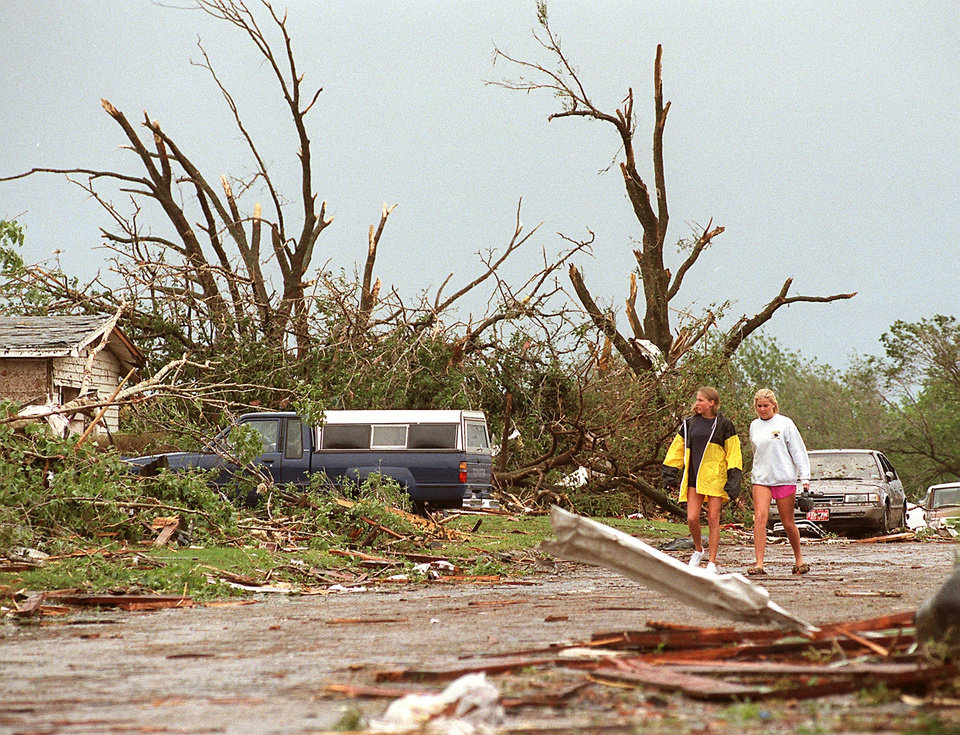 MAY 3, 1999 TORNADO: Tornado damage: Crystal Hogue, left, and Kim Case walk down SE 7th street around the 6000 blk to a friends house.