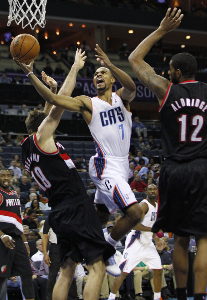 Photo - Charlotte Bobcats' Ramon Sessions (7) drives between Portland Trail Blazers' Joel Freeland (19) and LaMarcus Aldridge (12) during the first half of an NBA basketball game in Charlotte, N.C., Monday, Dec. 3, 2012. (AP Photo/Chuck Burton)