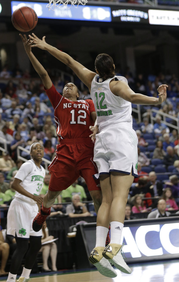 Photo - North Carolina State's Krystal Barrett, left, shoots over Notre Dame's Taya Reimer, right, during the first half of an NCAA college basketball semifinal game at the Atlantic Coast Conference tournament in Greensboro, N.C., Saturday, March 8, 2014. (AP Photo/Chuck Burton)