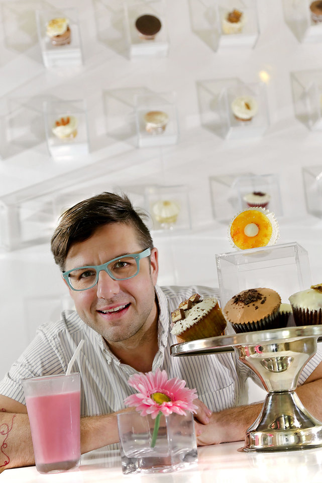 Photo - Chef Eric Smith is surrounded by cupcakes at Sara Sara Cupcakes, which he co-owns with his cousins. Photo by Chris Landsberger, The Oklahoman  CHRIS LANDSBERGER - CHRIS LANDSBERGER