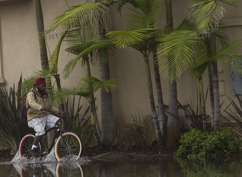 Photo - A cyclist drives the overflowed streets near the Pacific Coast Highway in the Sunset Beach area of Huntington Beach, Calif., Thursday, Dec. 13, 2012. Astronomical high tides have caused minor street flooding in some low-lying areas along the Southern California coast. (AP Photo/Damian Dovarganes)
