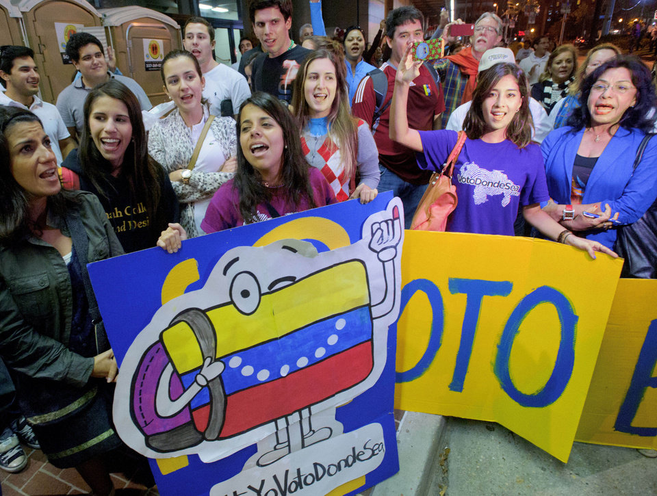 Venezuelan citizens living in the United States including Vanessa Dunn, left, holding Venezuela flag sign, and Lia Nunes, holding Voto (Vote) sign, from Miami, sing as they wait in line to vote at the New Orleans Ernest Morial Convention Center, in New Orleans, Sunday, Oct. 7, 2012. Hundreds of Venezuelans living in the U.S. streamed into New Orleans on Sunday to cast ballots in the presidential election in their homeland, many of them determined to end the 13-year reign of Hugo Chavez. With the country\'s consulate in Miami closed, thousands of Venezuelans traveled by bus, car and plane to cast their votes at the consulate in New Orleans. (AP Photo/Matthew Hinton)