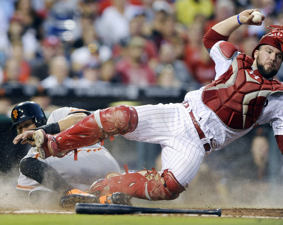Photo - Philadelphia Phillies catcher Cameron Rupp trips over San Francisco Giants' Michael Morse who is forced out at home on a Ryan Vogelsong ground out to third in the fourth inning of a baseball game on Monday, July 21, 2014, in Philadelphia. (AP Photo/Michael Perez)
