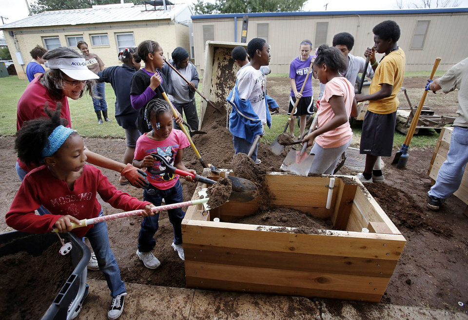 Photo - Soil is transferred from a trailer into a planter. Volunteers are planting a garden at Stanley Hupfeld Academy at Western Village. Photo by Jim Beckel, The Oklahoman.  Jim Beckel