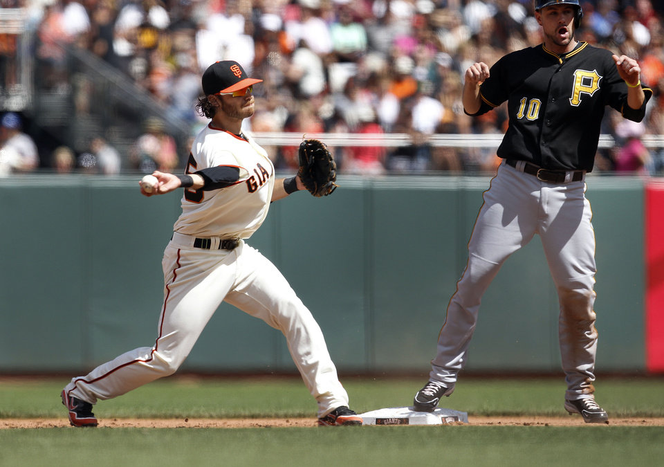 Photo - San Francisco Giants shortstop Brandon Crawford, left, throws to first completing a double play after forcing out Pittsburgh Pirates' Jordy Mercer, right, at second base in the sixth inning of a baseball game in San Francisco, Sunday, Aug. 25, 2013. (AP Photo/Tony Avelar)