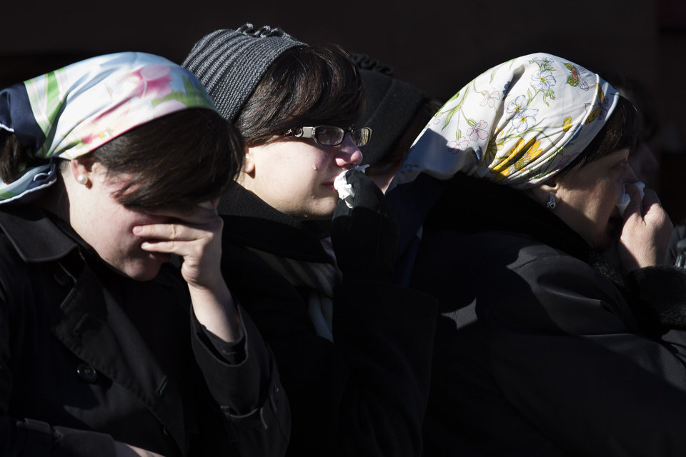 Photo - Members of the Satmar Orthodox Jewish community grieve at the funeral of two expectant parents who were killed in a car accident, Sunday, March 3, 2013, in the Brooklyn borough of New York. A driver struck the car early Sunday morning, killing both parents while their baby, who was born prematurely, survived and is in critical condition. (AP Photo/John Minchillo)
