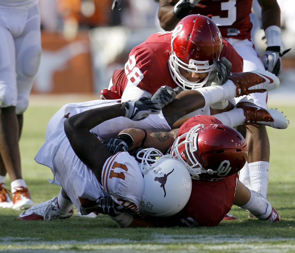Photo - OU's Travis Lewis, top, and Tom Wort bring down James Kirkendoll of Texas during the second half of the Red River Rivalry college football game between the University of Oklahoma Sooners (OU) and the University of Texas Longhorns (UT) at the Cotton Bowl on Saturday, Oct. 2, 2010, in Dallas, Texas. OU defeated Texas 28-20.    Photo by Bryan Terry, The Oklahoman
