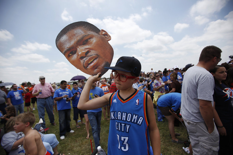 Photo - Jack Pitman, 11, of Oklahoma City, holds up a cutout of Kevin Durant's head during a welcome home rally for the Oklahoma City Thunder at a field near Will Rogers Airport in Oklahoma City, Friday, June 22, 2012.  Photo by Garett Fisbeck, The Oklahoman