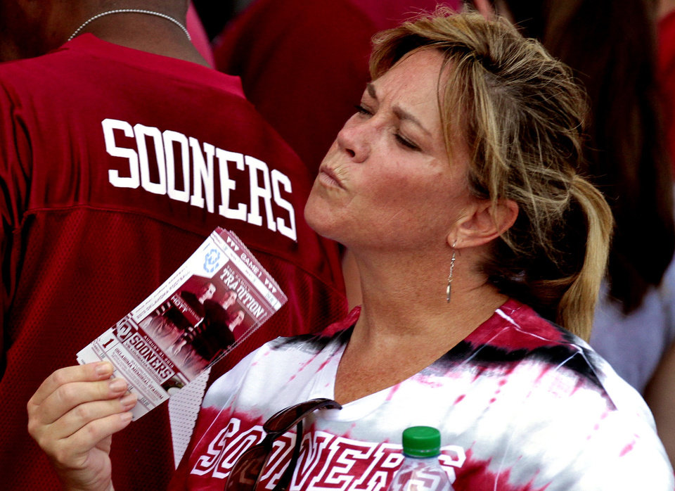 Suzanne Schroer, Leesummit, Mo. fans herself with her tickets as she waits to enter the stadium for the college football game where the University of Oklahoma Sooners (OU) play the University of Louisiana Monroe Warhawks at Gaylord Family-Oklahoma Memorial Stadium in Norman, Okla., on Saturday, Aug. 31, 2013. Photo by Steve Sisney, The Oklahoman