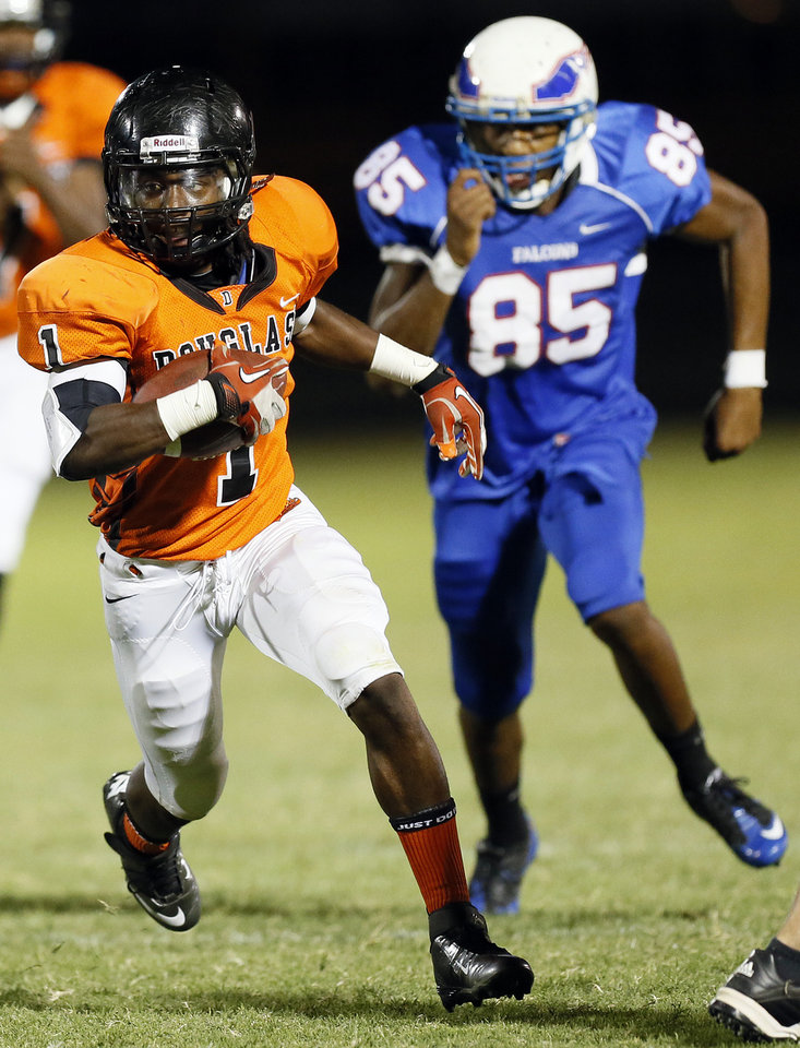 Photo - Douglass' Terry Harris (1) runs away from Millwood's Quincy Dotson (85) during the championship high school football scrimmage of the All-City Preview between Douglass and Millwood at Moses F. Miller Stadium in Oklahoma City, Friday, Aug. 24, 2012. Photo by Nate Billings, The Oklahoman