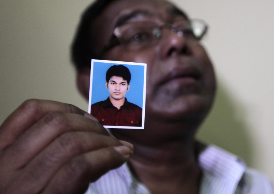 Photo -   Bangladeshi Quazi Ahsanullah displays a photograph of his son Quazi Mohammad Rezwanul Ahsan Nafis as he weeps in his home in the Jatrabari neighborhood in north Dhaka, Bangladesh, Thursday, Oct. 18, 2012. The FBI arrested 21-year-old Nafis on Wednesday after he tried to detonate a fake 1,000-pound (454-kilogram) car bomb, according to a criminal complaint. His family said Thursday that Nafis was incapable of such actions. (AP Photo/A.M. Ahad)