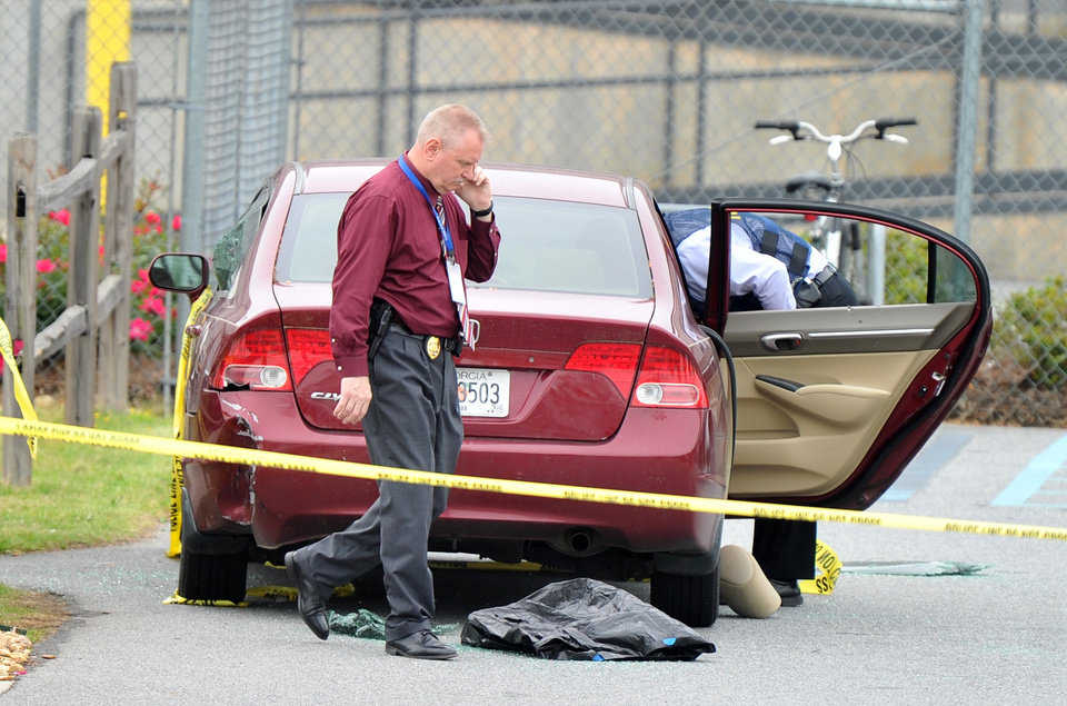 Photo - Police officials search a car located at the scene of the shooting that took place at a FedEx facility in Kennesaw, Ga., on Tuesday, April 29, 2014.  A shooter described as being armed with an assault rifle and having bullets strapped across his chest