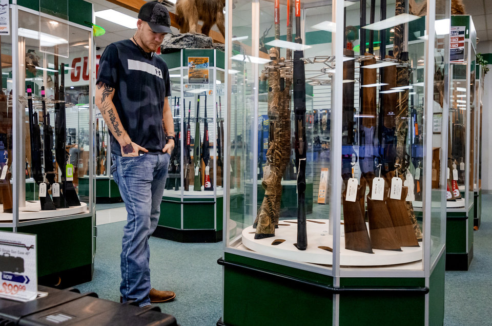 Photo - Colton Vetter looks at the selection of guns at H&H Shooting Sports in Oklahoma City, Okla. on Wednesday, March 18, 2020.  [Chris Landsberger/The Oklahoman]
