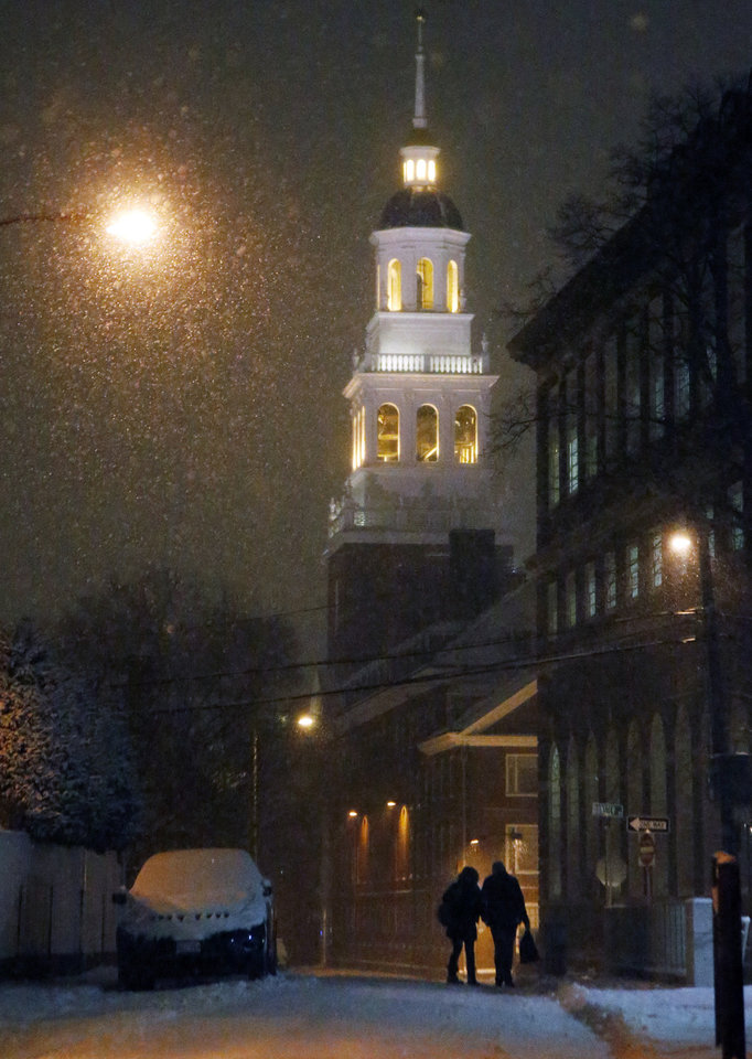 Photo - A couple walk as snow falls in Harvard Square in Cambridge, Mass. Tuesday, Jan. 21, 2014. Heavy snow has been forecast and a blizzard warning was posted for portions of Massachusetts. (AP Photo/Elise Amendola)