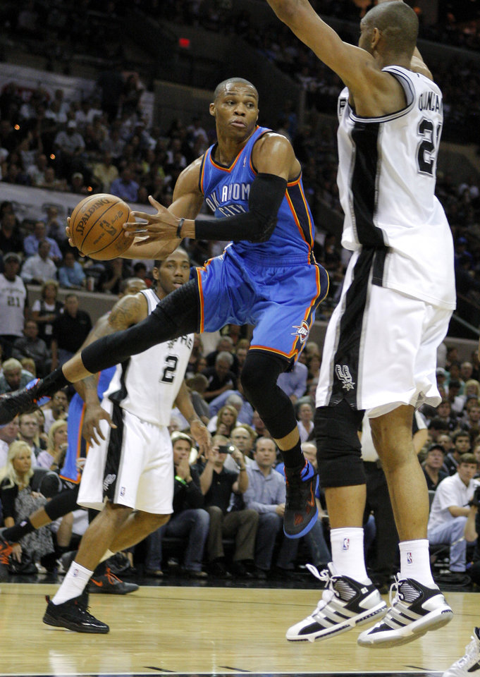 Photo - Oklahoma City's Russell Westbrook (0) tries to pass the ball around San Antonio's Tim Duncan (21) during Game 2 of the Western Conference Finals between the Oklahoma City Thunder and the San Antonio Spurs in the NBA playoffs at the AT&T Center in San Antonio, Texas, Tuesday, May 29, 2012. Photo by Bryan Terry, The Oklahoman