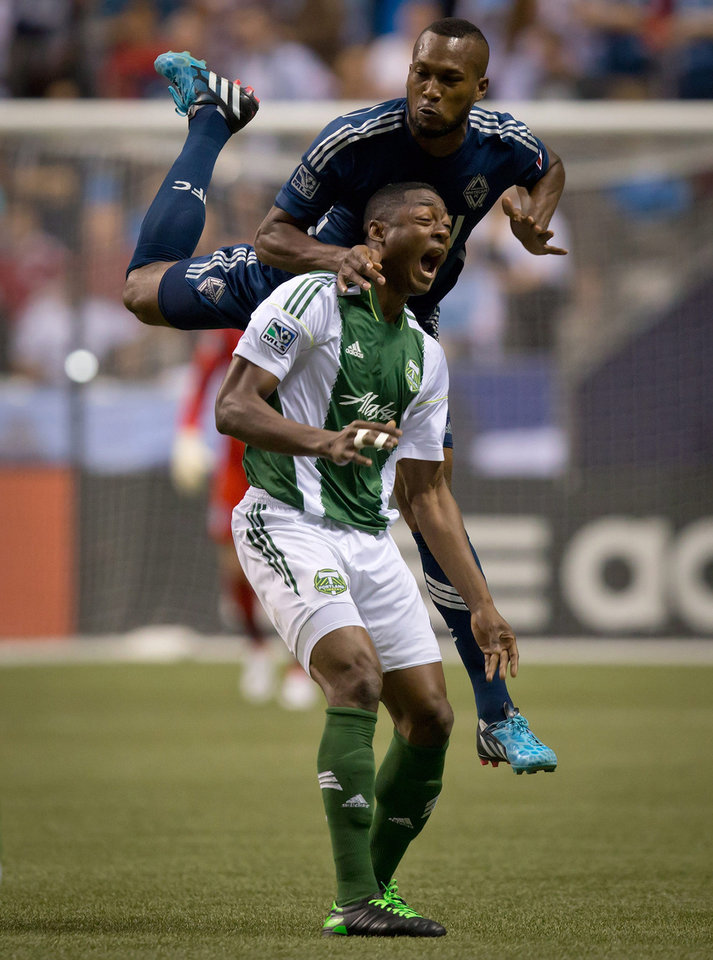 Photo - Portland Timbers' Fanendo Adi, bottom, of Nigeria, reacts as Vancouver Whitecaps' Kendall Watson, of Costa Rica, collides with him after jumping for the ball during the first half of an MLS soccer game in Vancouver, British Columbia, on Saturday, Aug. 30, 2014. (AP Photo/The Canadian Press, Darryl Dyck)