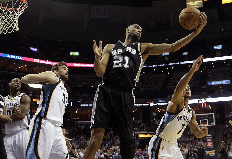 Photo - San Antonio Spurs forward Tim Duncan (21) grabs a rebound against Memphis Grizzlies defenders Darrell Arthur (00), Marc Gasol (33), of Spain, and Jerryd Bayless (7) in the first half of an NBA basketball game on Friday, Jan. 11, 2013, in Memphis, Tenn. (AP Photo/Lance Murphey)