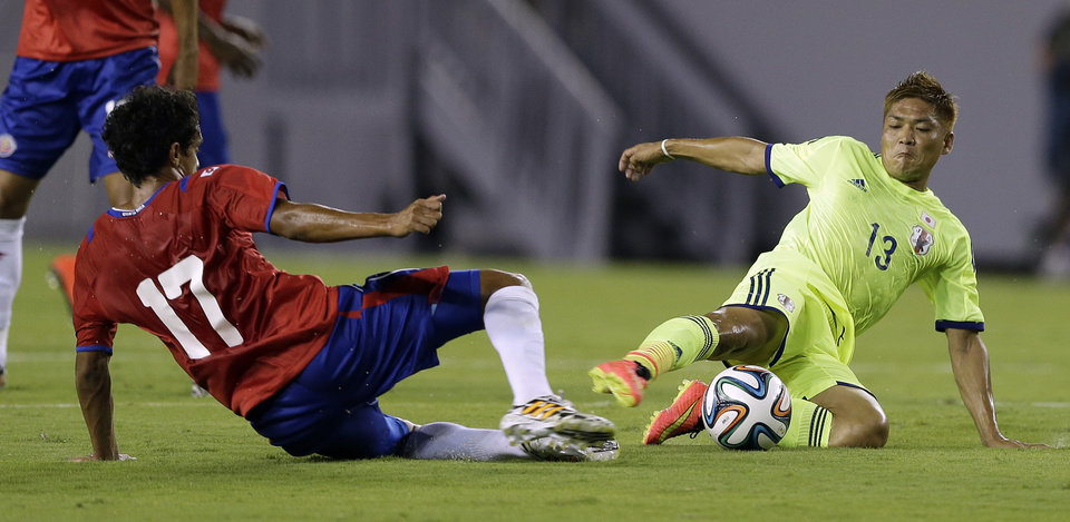Photo - Japan forward Yoshito Okubo (13) reaches for the ball in front of Costa Rica midfielder Yeltsin Tejeda (17) during the first half of a friendly soccer match Monday, June 2, 2014, in Tampa, Fla. (AP Photo/Chris O'Meara)