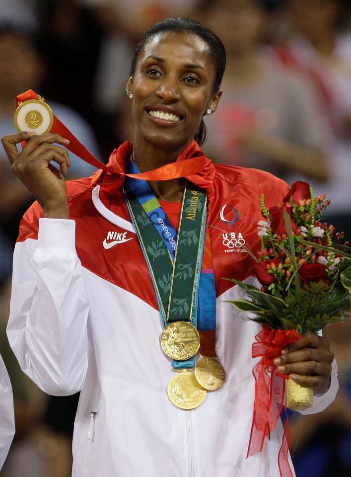 Photo - FILE - In this Aug. 23, 2008, file photo, USA player Lisa Leslie holds up the fourth of her gold medals after receiving gold for beating Australia in the women's basketball gold medal game at the Beijing 2008 Olympics in Beijing. Leslie headlines the 2015 women's basketball Hall of Fame induction class announced Saturday, July 19, 2014,  She is joined by former Houston Comets star Janeth Arcain, University of Georgia standout Janet Harris, former Duke coach Gail Goestenkors, longtime Oregon high school coach Brad Smith and Oklahoma State coach Kurt Budke, who was killed in a plane crash in 2011.  (AP Photo/Dusan Vranic, File