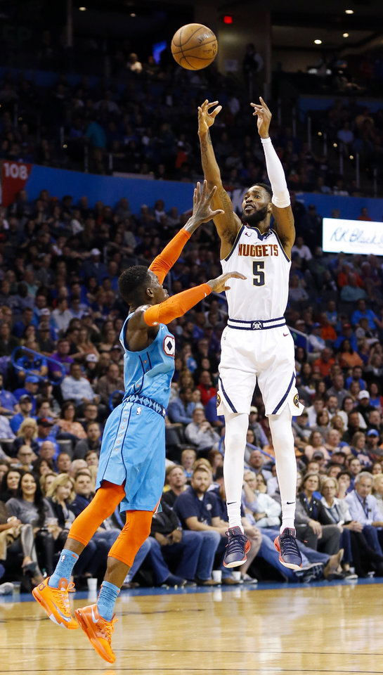Photo - Denver's Will Barton (5) makes a three-point shot over Oklahoma City's Dennis Schroder (17) in the fourth quarter during an NBA basketball game between the Denver Nuggets and the Oklahoma City Thunder at Chesapeake Energy Arena in Oklahoma City, Friday, March 29, 2019. Denver won 115-105. Photo by Nate Billings, The Oklahoman